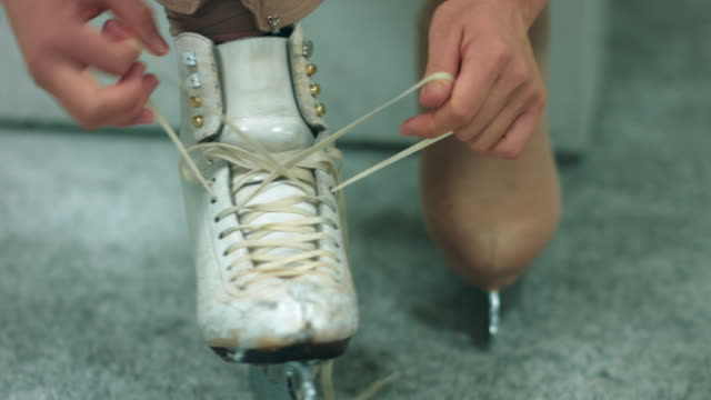 a female figure skater lacing up skates - ice skating stock videos and b-roll footage