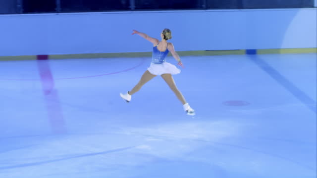 slo mo ts female figure skater performing a jump - ice skating stock videos and b-roll footage