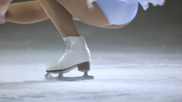 slo mo female figure skater performing a sit spin - ice rink stock videos & royalty-free footage