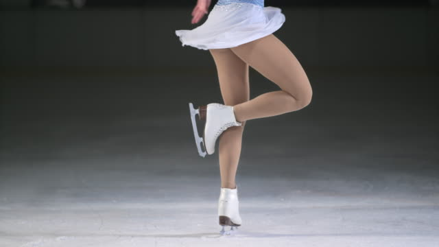 slo mo ld female figure skater performing one foot spin - ice skating stock videos and b-roll footage