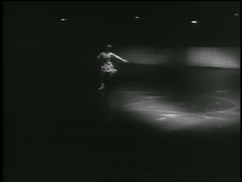 b/w 1935 female figure skater skating in out of spotlight / she starts to spin - 1935 stock videos & royalty-free footage