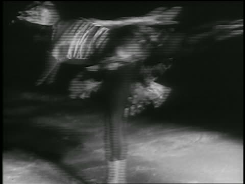 b/w 1935 female figure skater spinning on one leg then crouching spinning - 1935 stock videos & royalty-free footage