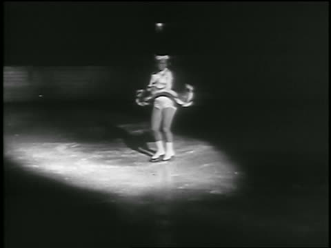 b/w 1935 female figure skater spinning then skating in spotlight on ice rink - 1935 stock videos & royalty-free footage