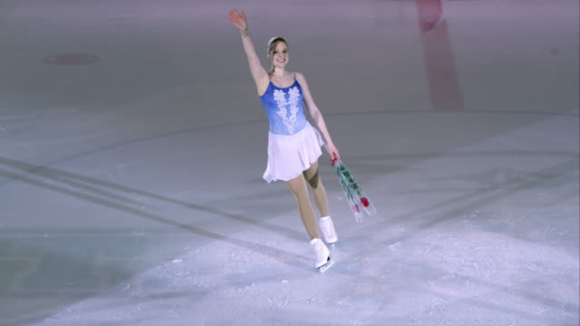 slo mo female figure skater waving to her audience - figure skating stock videos and b-roll footage