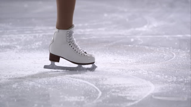 slo mo ts female figure skates in a crossfoot spin - ice rink stock videos & royalty-free footage