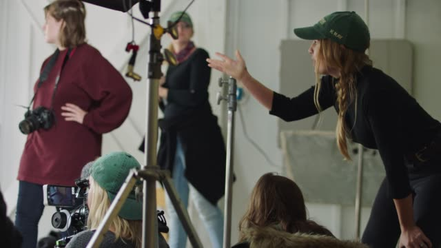 vídeos de stock e filmes b-roll de female filmmaker collaborates with cinematographer and oversees production on sound stage with all-female​ film crew. - montagem de filme estúdio de cinema
