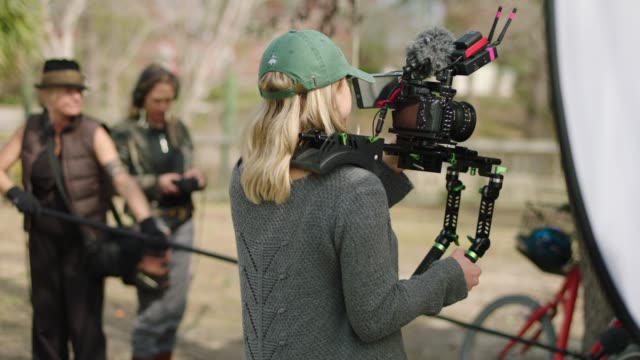 SLO MO. Female filmmaker holds camera rig while boom operator and sound mixer stand in background on film set with all female crew.
