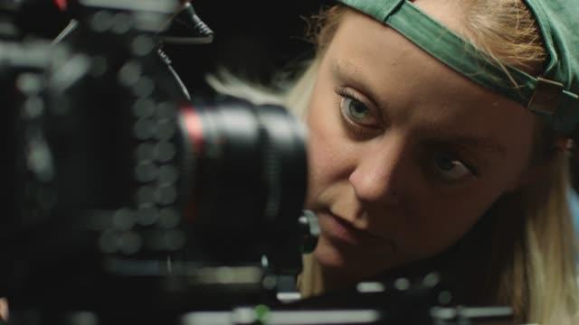 cu slo mo. female filmmaker inspects camera lens on film set. - filmkamera stock-videos und b-roll-filmmaterial