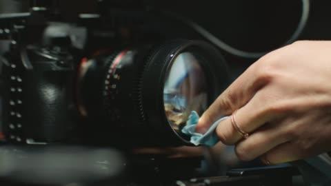 vídeos y material grabado en eventos de stock de ecu slo mo. female filmmaker pulls focus and carefully cleans camera lens with microfiber cleaning cloth. - stock video - film camera