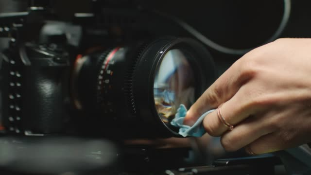 ecu slo mo. female filmmaker pulls focus and carefully cleans camera lens with microfiber cleaning cloth. - stock video - crew stock videos & royalty-free footage