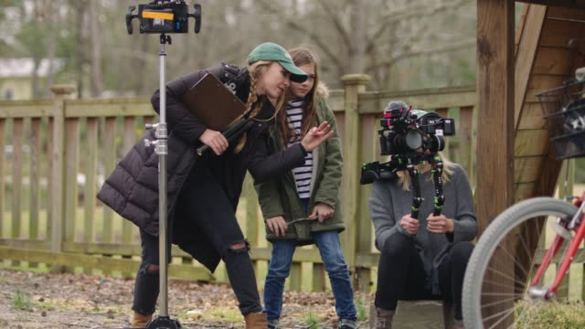Female producer and cinematographer with shoulder mount camera rig offer guidance to young girl learning how to direct on a professional film set.