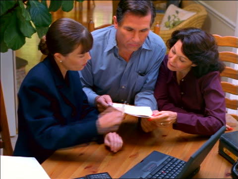 vidéos et rushes de female financial adviser with laptop handing papers to middle aged couple sitting at kitchen table - homme dans un groupe de femmes