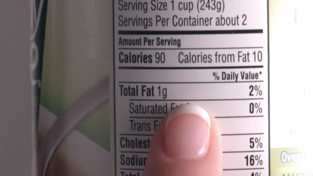ecu female finger follows text on nutrition label displayed on backside of can of food - label stock videos & royalty-free footage