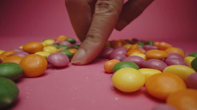ピンクの背景にキャンディーの束を歩く女性の指 - ジェリービーンズ点の映像素材/bロール