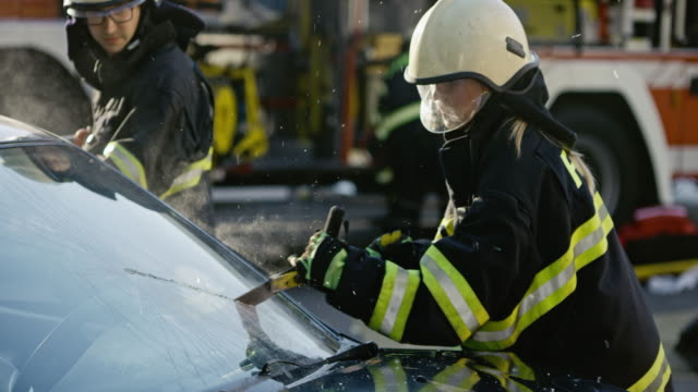 slo mo female firefighter cutting the windshield of the car - females stock videos & royalty-free footage