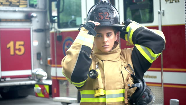 stockvideo's en b-roll-footage met vrouwelijke brandweerman in brandbeschermingspak, helm - brandweerman
