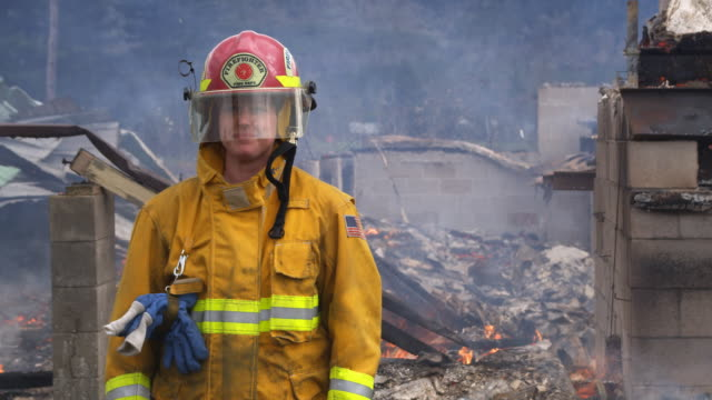 female firefighter in front of smoldering ruins of a totally destroyed house - firefighter stock videos and b-roll footage