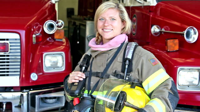 vídeos de stock e filmes b-roll de female firefighter standing in front of fire engines - bombeiro