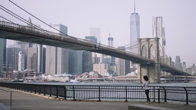 female fitness model training outside in new york city with skyline and brooklyn bridge in background - マンハッタン点の映像素材/bロール