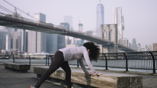 Female fitness model training outside in New York City with skyline and Brooklyn Bridge in background