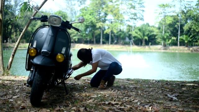 vídeos y material grabado en eventos de stock de hembra fijando un scooter en el parque cerca del lago. - examinar