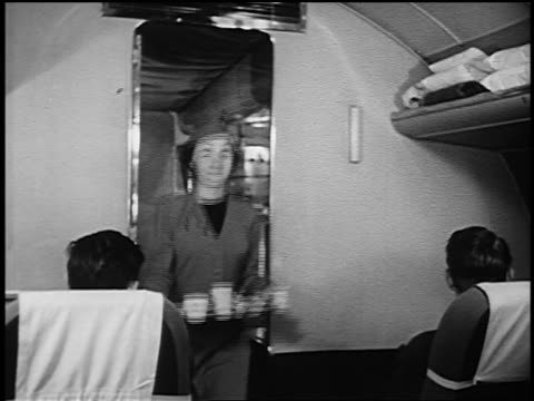 b/w 1951 female flight attendant carrying tray of food + beverages exiting galley on airliner - crew stock videos & royalty-free footage
