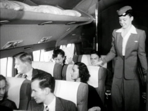 transportation female flight attendant checking on passengers in first class seats of dc6 giving pillow to woman handing another woman copy of 'life'... - air stewardess stock videos & royalty-free footage