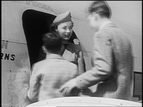 b/w 1951 female flight attendant greeting two boys entering airliner (teen boy could be used as man) - 1951 stock-videos und b-roll-filmmaterial