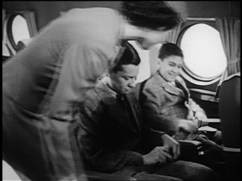 b/w 1951 female flight attendant helping two boys adjust seat belts on airliner - yorkville illinois stock videos & royalty-free footage