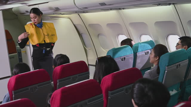 female flight attendant in airplane explains rules about safety during take off and in case of any accident or crash - equipaggio video stock e b–roll