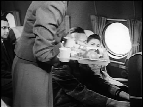 B/W 1951 female flight attendant serving tray of food to boy sitting on airliner next to teen boy