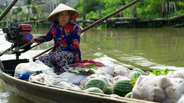 female floating market trader transporting water melons vietnam - tourism stock videos & royalty-free footage