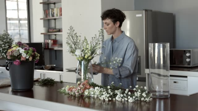 female florist arranging white flowers in vase at home - scegliere video stock e b–roll