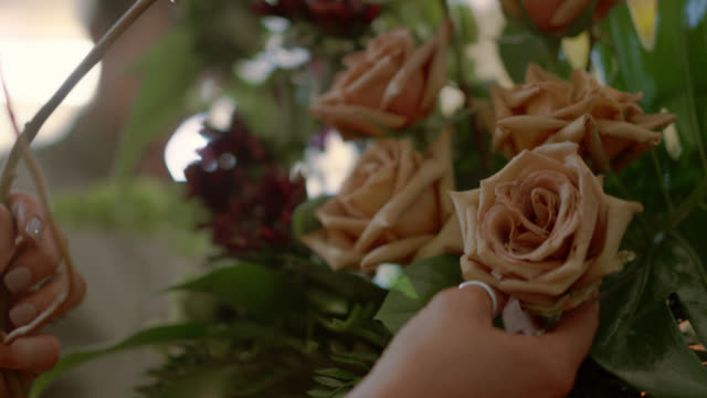 female flower shop owner puts a rose into a bouquet for a customer - bouquet stock videos & royalty-free footage