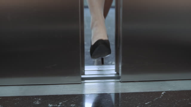 slo mo ds female foot stopping the elevator door - urgency stock videos & royalty-free footage