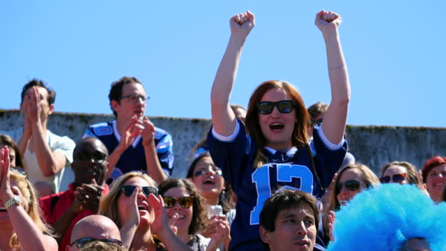 ms female football fan standing up in crowd cheering during game - shirt stock videos & royalty-free footage
