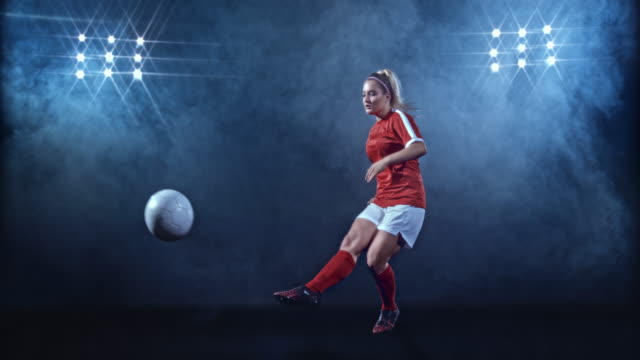 slo mo ld female football player in red jersey kicking the ball on misty black background - females stock videos & royalty-free footage