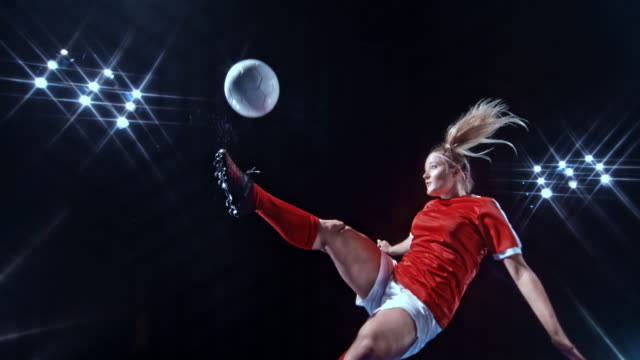 SLO MO LD Female football player kicking the ball in the air on black background