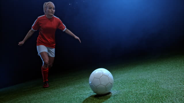 SPEED RAMP Female football player kicking the ball in the field at night