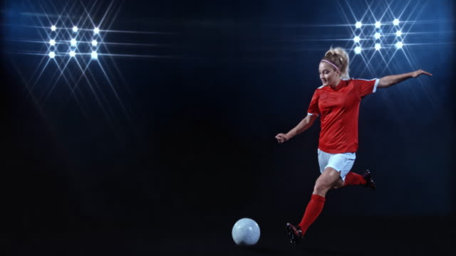 slo mo ld female football player kicking the ball on black background - kicking stock videos & royalty-free footage
