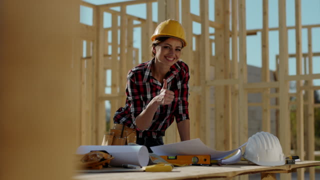 Female foreman holding blueprints and showing thumbs up