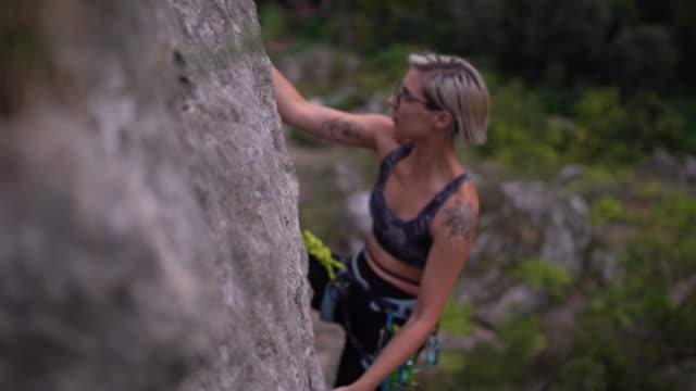 weibliche freiklettererin ist entschlossen, an die spitze des felsens zu gelangen - hoch allgemeine beschaffenheit stock-videos und b-roll-filmmaterial