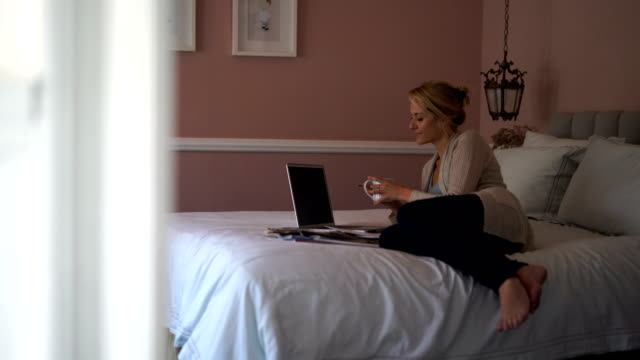female freelancer working on bed at home - hot desking stock videos & royalty-free footage
