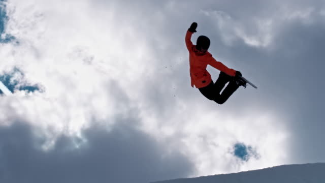 slo mo female freestyle snowboarder grabbing her snowboard while airborne in the half-pipe - half pipe stock videos & royalty-free footage