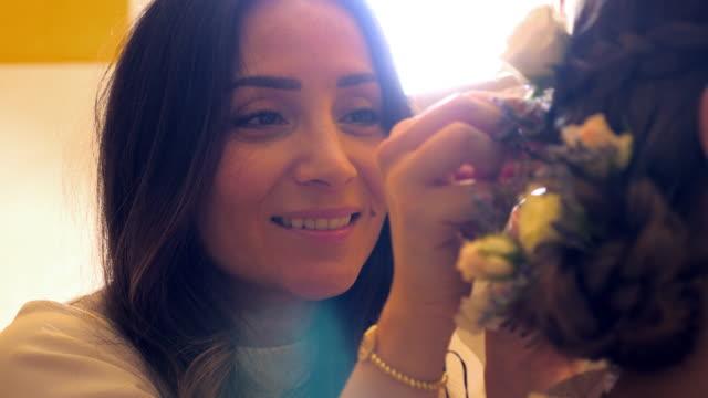 cu female friend helping bride put flowers in hair before wedding - preparation stock videos & royalty-free footage