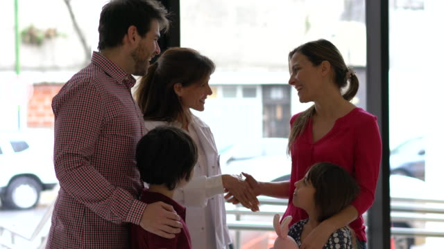 female friendly doctor greeting family with two children at the entrance of the hospital very cheerfully and then leaving - casual clothing video stock e b–roll