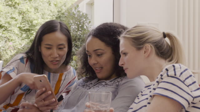 Female friends  are looking at mobile phone, sitting on sofa in livingroom.