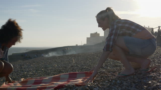 female friends are puting down blanket on beach for sitting on. - brighton england stock videos and b-roll footage