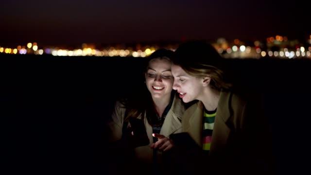 vídeos de stock, filmes e b-roll de os amigos fêmeas estão surfando a rede na noite - mensagem de texto