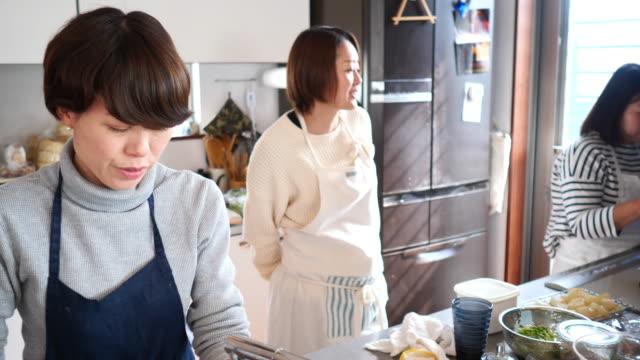 昼食パーティーのために料理の女性の友人 - mature adult点の映像素材/bロール